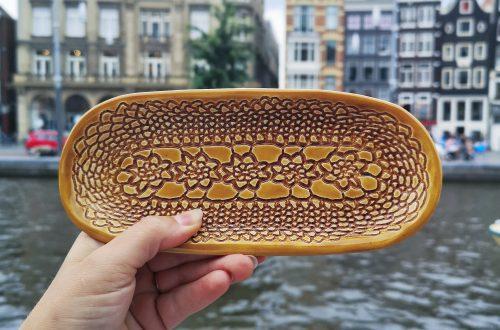 Handgemaakte keramische schaal met cognac kleurig glazuur en gemaakt door de afdruk van een kanten kleedje, met Amsterdamse grachtenpanden op de achtergrond.