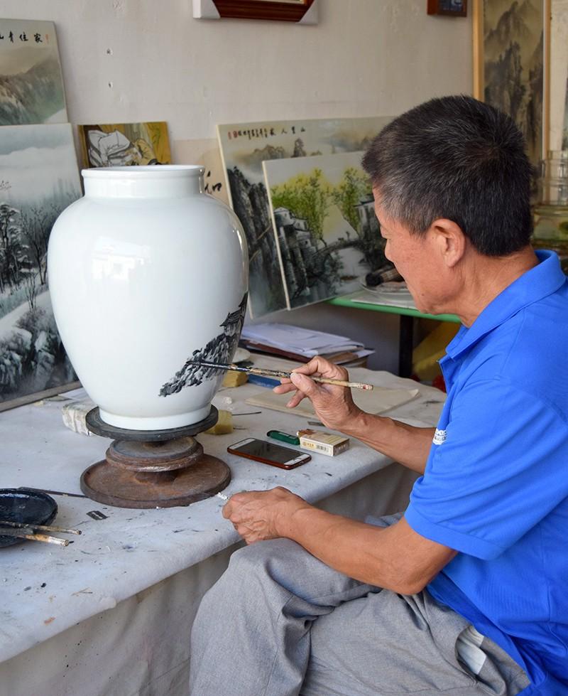 Master in porselein beschilderen in Jingdezhen