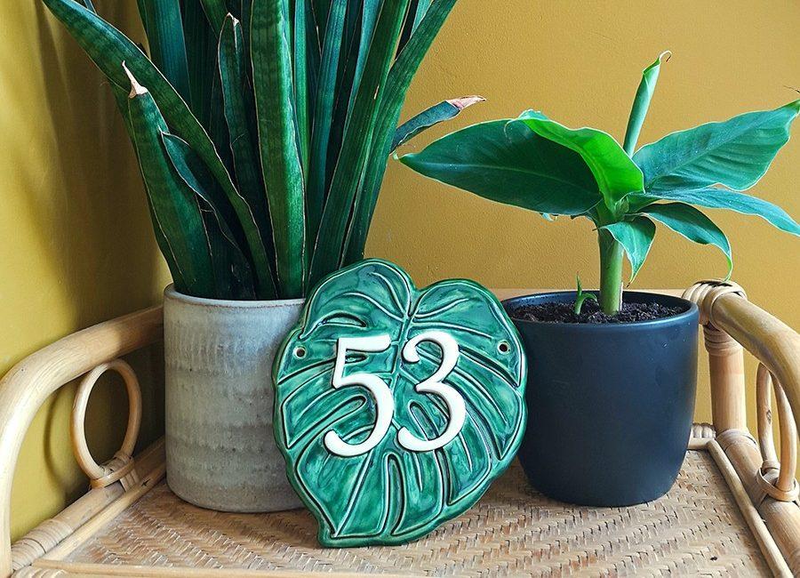 Huisnummer 53 met groen monstera plant blad als achtergrond.